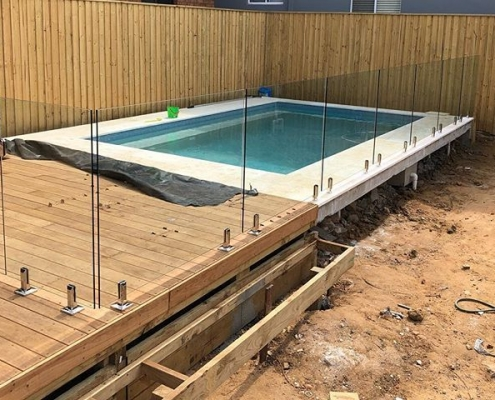 timber mount and core drilled glass pool fence